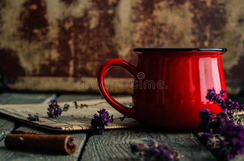 Εκλεκτής ποιότητας κόκκινο φλυτζάνι του τσαγιού με τα ξύλινα χορτάρια υποβάθρου και oregano στοκ φωτογραφία