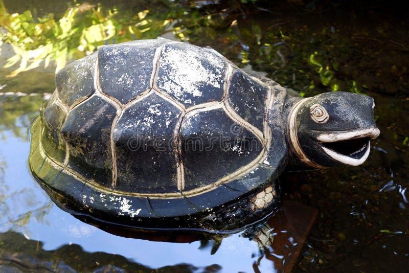 Εκλεκτής ποιότητας μαύρο γλυπτό χελωνών που απομονώνεται στη λίμνη στοκ φωτογραφία
