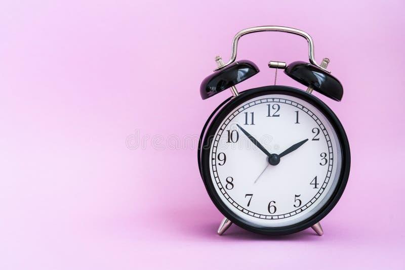 Εκλεκτής ποιότητας μαύρο ξυπνητήρι στο ρόδινο υπόβαθρο στοκ φωτογραφία