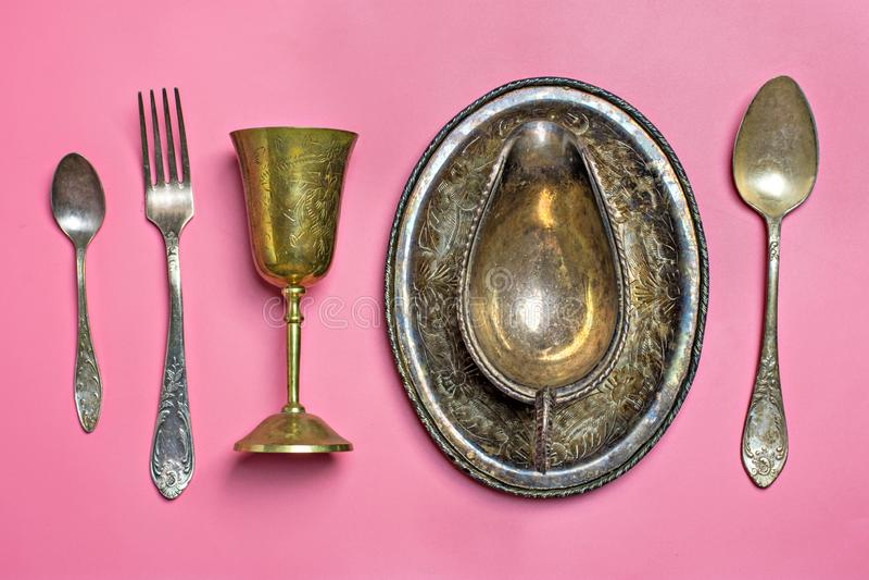 Εκλεκτής ποιότητας μεγάλο και μικρό κουτάλι εργαλείων κουζινών χαλκού, δίκρανο, κύπελλο σάλτσας, γυαλί σε ένα ρόδινο υπόβαθρο στοκ φωτογραφίες με δικαίωμα ελεύθερης χρήσης