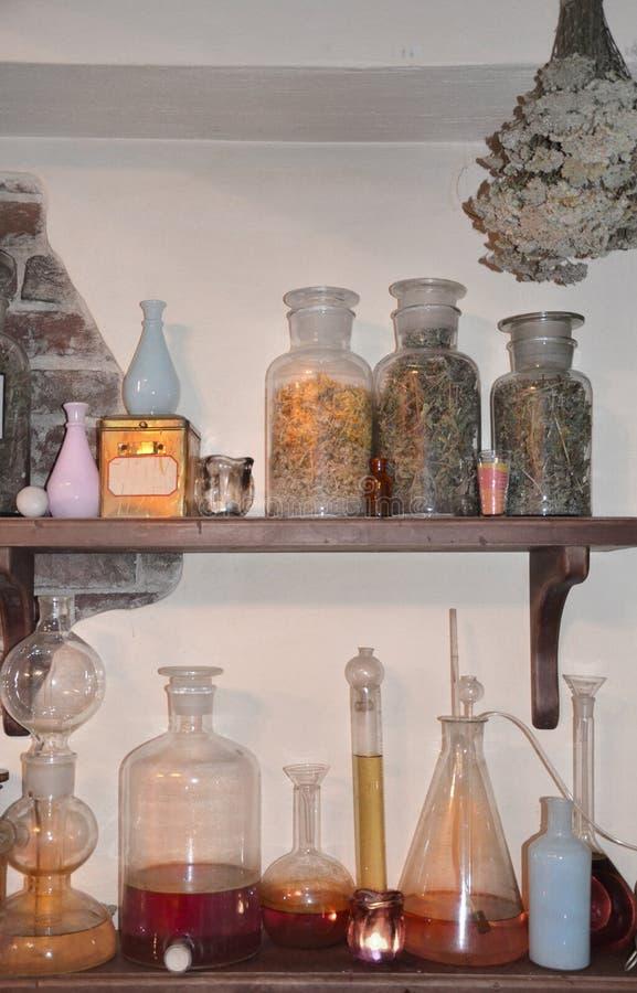 Εκλεκτής ποιότητας μπουκάλια με τα χορτάρια στο ράφι σε ένα παλαιό φαρμακείο στοκ εικόνα