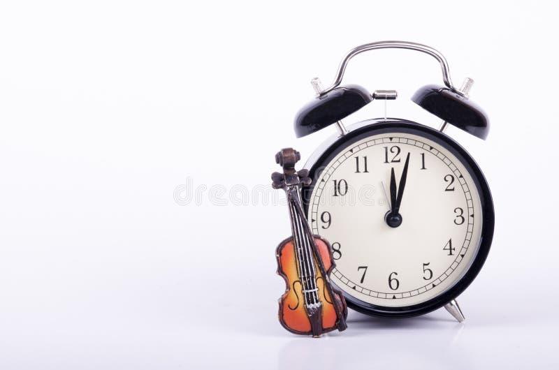 Εκλεκτής ποιότητας ξυπνητήρι και μικρό βιολί στο άσπρο υπόβαθρο στοκ εικόνες με δικαίωμα ελεύθερης χρήσης