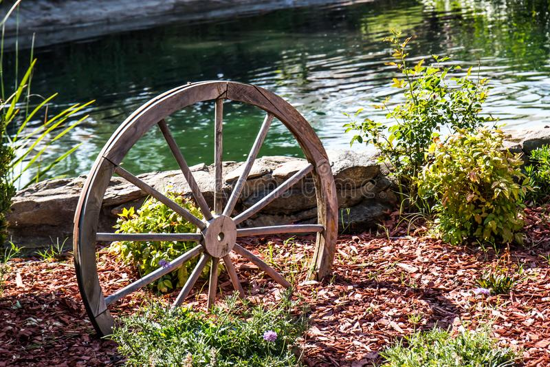 Εκλεκτής ποιότητας ξύλινη ρόδα στον κήπο δίπλα στη λίμνη στοκ εικόνες