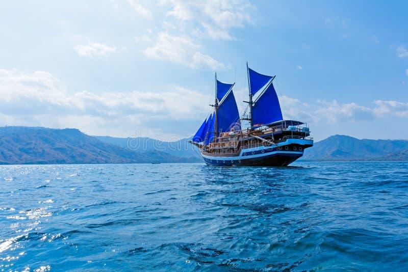 Εκλεκτής ποιότητας ξύλινο σκάφος με τα μπλε πανιά στοκ εικόνες