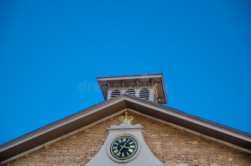 Εκλεκτής ποιότητας πίσω ρολόι προσώπου με τους χρυσούς ρωμαϊκούς αριθμούς σε ένα παλαιό κτήριο τούβλου με το υπόβαθρο μπλε ουρανο στοκ εικόνες