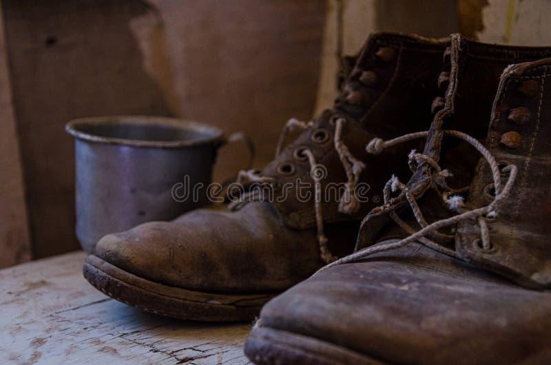 Εκλεκτής ποιότητας παλαιές λειτουργώντας μπότες και παλαιό φλυτζάνι στοκ φωτογραφίες