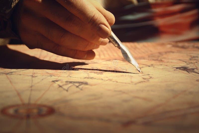 Εκλεκτής ποιότητας παλαιός χάρτης θησαυρών, μάνδρα στα χέρια του χαρτογράφου, σχέδιο χαρτών στοκ εικόνα με δικαίωμα ελεύθερης χρήσης