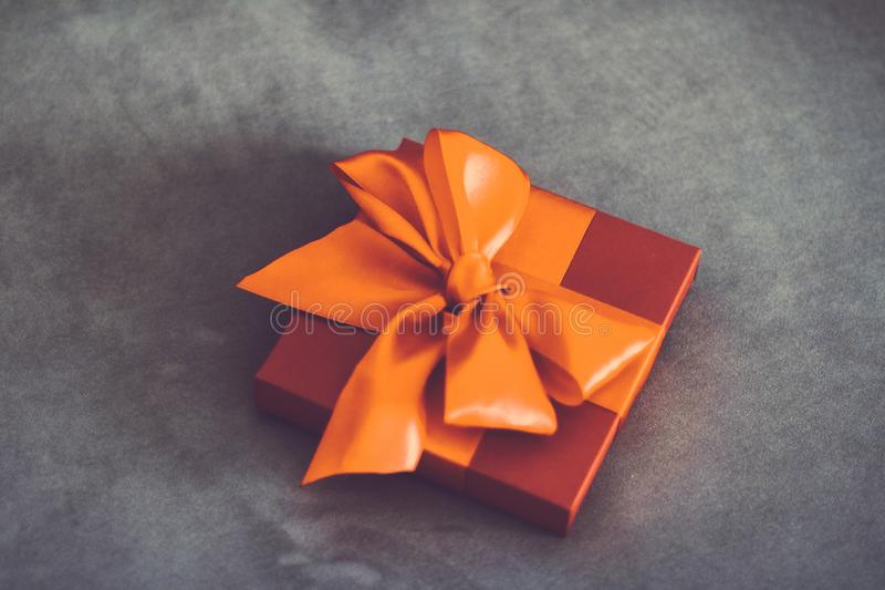 Εκλεκτής ποιότητας πολυτέλειας κιβώτιο δώρων διακοπών πορτοκαλί με την κορδέλλα μεταξιού και το ντεκόρ τόξων, Χριστουγέννων ή ημέ στοκ φωτογραφία