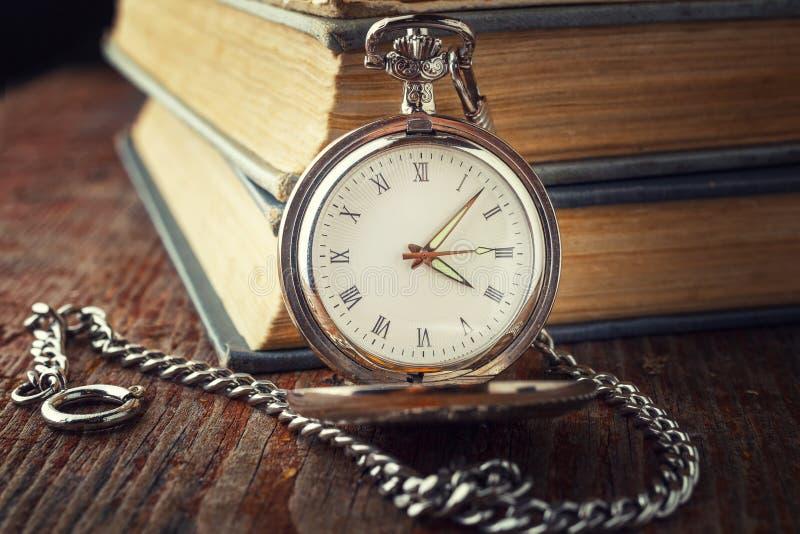 Εκλεκτής ποιότητας ρολόι σε μια αλυσίδα σε ένα υπόβαθρο των παλαιών βιβλίων στοκ εικόνες με δικαίωμα ελεύθερης χρήσης