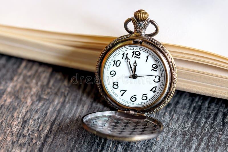 Εκλεκτής ποιότητας ρολόι τσεπών με το ανοικτό βιβλίο στοκ φωτογραφία