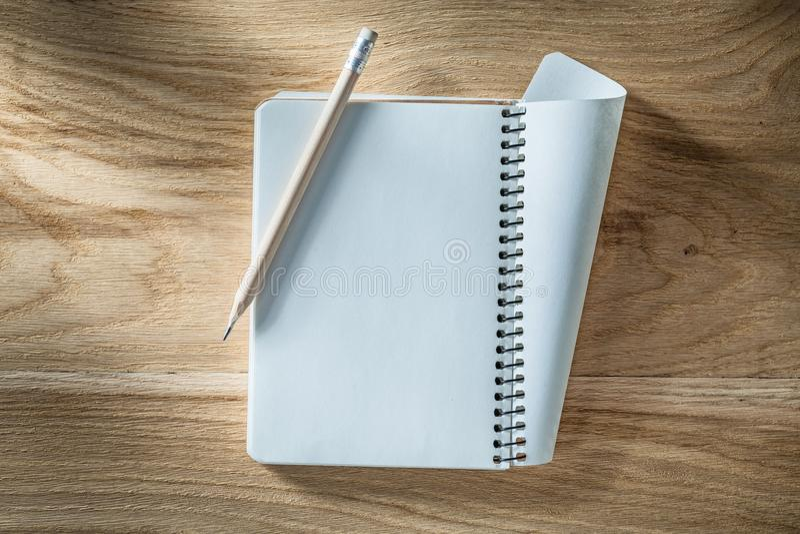 Εκλεκτής ποιότητας σπειροειδές κενό μολύβι σημειωματάριων στον ξύλινο πίνακα στοκ φωτογραφία