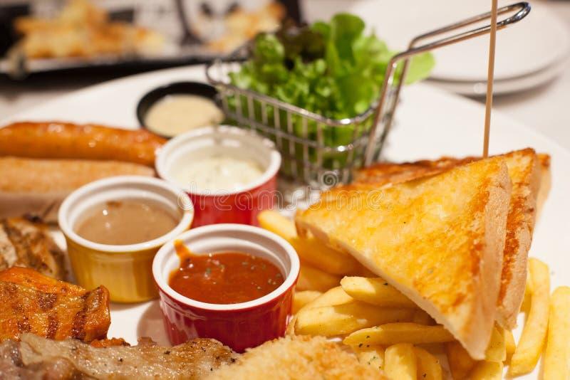 Εκλεκτικά τρόφιμα, τηγανιτές πατάτες και ψημένες βουτύρου να πλαισιώσει ψωμιού μπριζόλες και κατάταξη λουκάνικων με τις ποικιλίες στοκ εικόνες