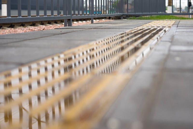 Εκλεκτική εστίαση στους αφής δείκτες για τυφλός και με οπτική αναπηρία μετά από τη βροχή που βρίσκεται στο πέρασμα σιδηροδρόμων στοκ φωτογραφία με δικαίωμα ελεύθερης χρήσης