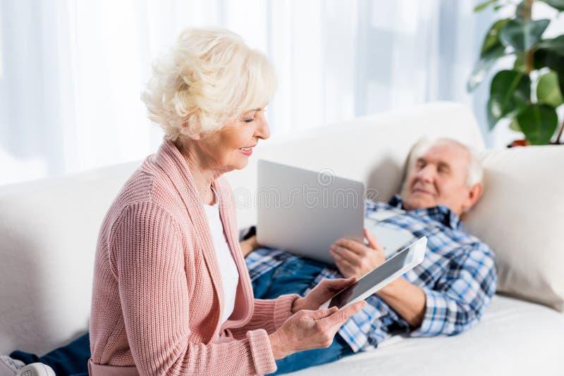 εκλεκτική εστίαση της ανώτερων συζύγου και του συζύγου που χρησιμοποιούν τις ψηφιακές συσκευές στοκ φωτογραφίες με δικαίωμα ελεύθερης χρήσης