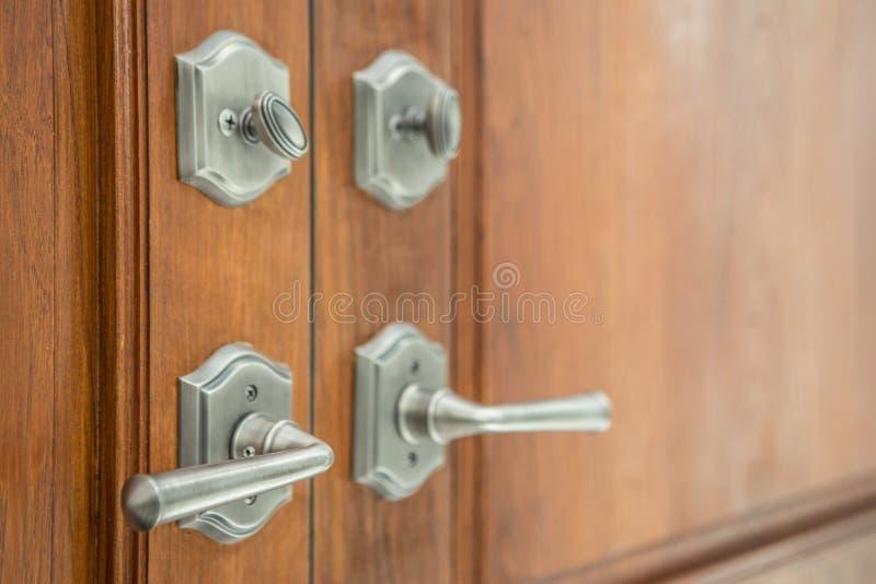 Εκλεκτική εστίαση των λαβών πορτών πολυτέλειας στην ξύλινη πόρτα στοκ εικόνες