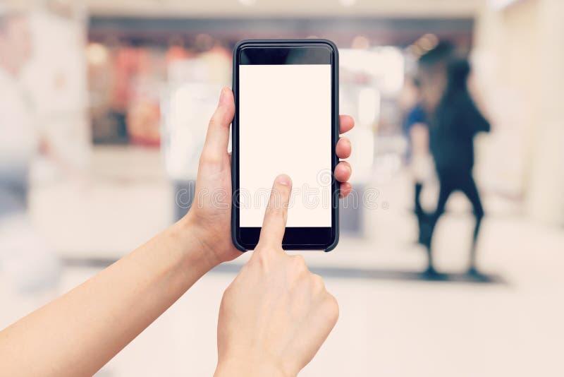 Εκμετάλλευση γυναικών χεριών και χρησιμοποίηση του τηλεφώνου με το θολωμένο υπόβαθρο στο SH στοκ φωτογραφία