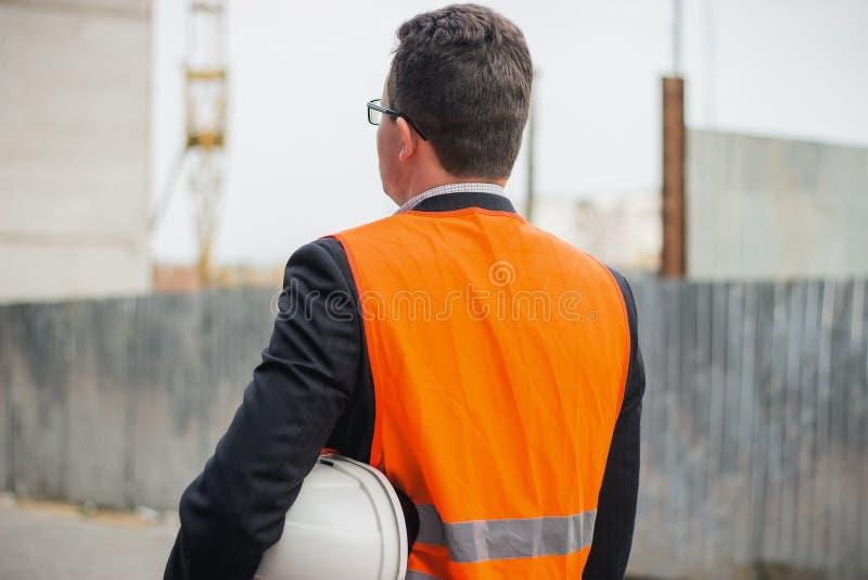Εκμετάλλευση εργαζομένων ή μηχανικών στο κράνος χεριών για την ασφάλεια εργαζομένων στο υπόβαθρο των νέων πολυκατοικιών πολυόροφω στοκ φωτογραφία με δικαίωμα ελεύθερης χρήσης