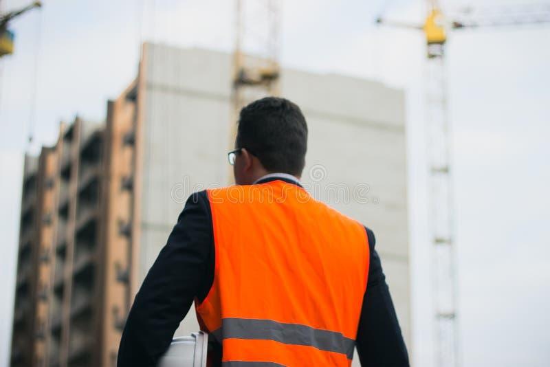 Εκμετάλλευση εργαζομένων ή μηχανικών στο κράνος χεριών για την ασφάλεια εργαζομένων στο υπόβαθρο των νέων πολυκατοικιών πολυόροφω στοκ φωτογραφίες
