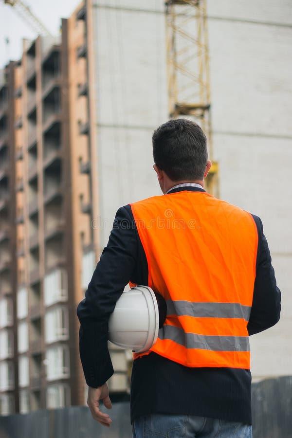 Εκμετάλλευση εργαζομένων ή μηχανικών στο κράνος χεριών για την ασφάλεια εργαζομένων στο υπόβαθρο των νέων πολυκατοικιών πολυόροφω στοκ φωτογραφίες με δικαίωμα ελεύθερης χρήσης
