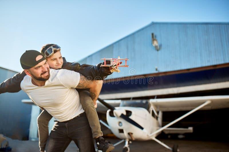 Εκμετάλλευση μπαμπάδων στην πλάτη του λίγος γιος με το χειροποίητο αεροπλάνο παιχνιδιών, υπόστεγο εξωτερικού παιχνιδιού στοκ φωτογραφίες