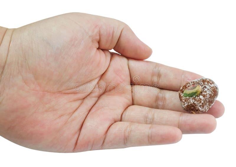 Εκμετάλλευση χεριών γύρω από τη σφαίρα καραμελών σοκολάτας με το φυστίκι στοκ εικόνα