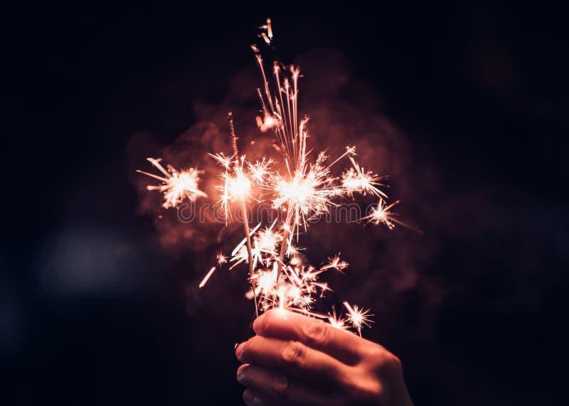 Εκμετάλλευση χεριών που καίει το φύσημα Sparkler σε ένα μαύρο υπόβαθρο στο nig στοκ εικόνα