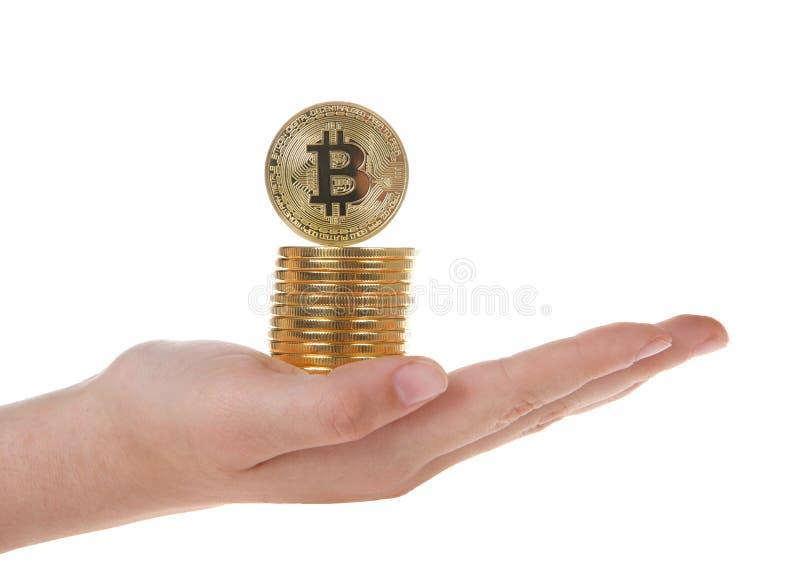 Εκμετάλλευση χεριών που συσσωρεύεται bitcoins ένα που ισορροπεί στην κορυφή λοξά στοκ εικόνες