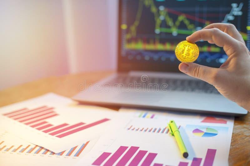 Εκμετάλλευση χεριών bitcoin μπροστά από το lap-top και τα διαγράμματα στο γραφείο στοκ φωτογραφία