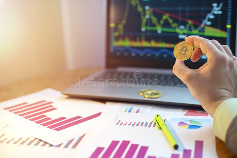 Εκμετάλλευση χεριών bitcoin μπροστά από το lap-top και τα διαγράμματα στο γραφείο στοκ εικόνες
