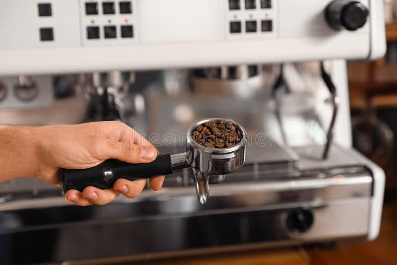 Εκμετάλλευση Barista portafilter με τα φασόλια καφέ κοντά στη μηχανή, κινηματογράφηση σε πρώτο πλάνο στοκ φωτογραφία με δικαίωμα ελεύθερης χρήσης
