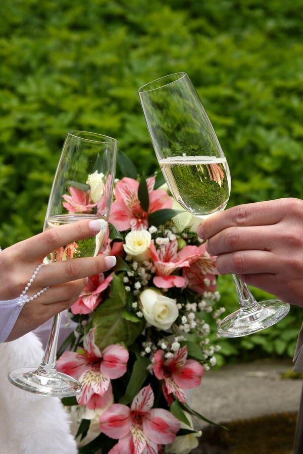 εκμετάλλευση νεόνυμφων φρυγανιά σαμπάνιας Γαμήλια γυαλιά στα χέρια τους στοκ εικόνες