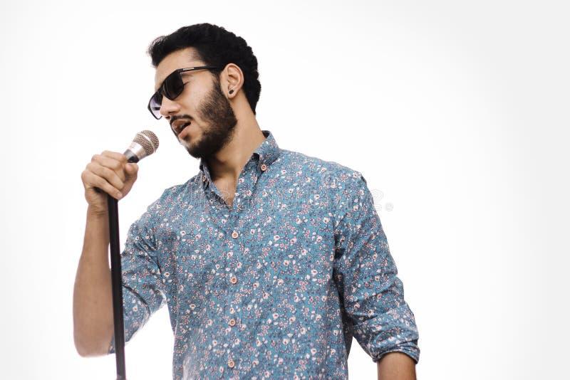 Εκμετάλλευση Mic νεαρών άνδρων που φορά τα γυαλιά και που τραγουδά ένα τραγούδι στοκ φωτογραφία με δικαίωμα ελεύθερης χρήσης