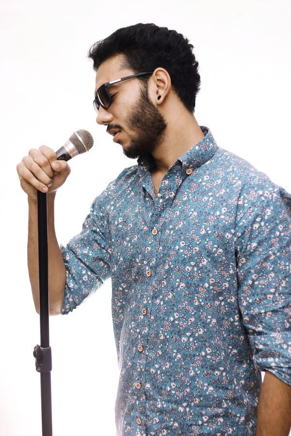 Εκμετάλλευση Mic νεαρών άνδρων που φορά τα γυαλιά και που τραγουδά ένα τραγούδι στοκ φωτογραφία