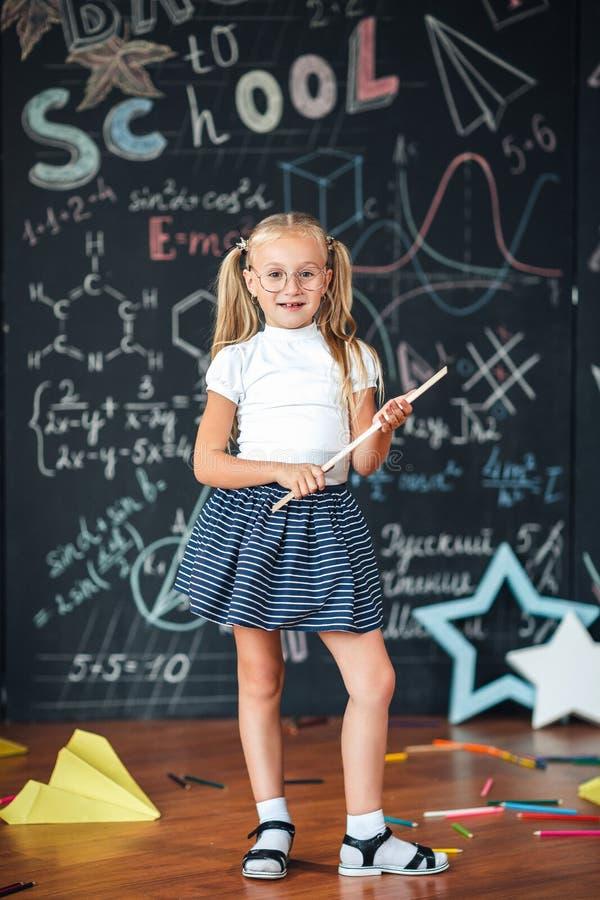 Εκπαίδευση και σχολική έννοια Η μαθήτρια, ξανθή στη σχολική στολή με τα άσπρα τόξα και τα γυαλιά κρατά τον κυβερνήτη στον πίνακα  στοκ φωτογραφία με δικαίωμα ελεύθερης χρήσης