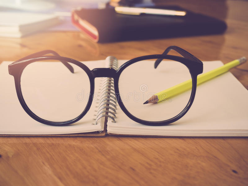 Εκπαίδευση και έννοια γραφείων Σημειωματάριο και eyeglasses μολυβιών στοκ εικόνες