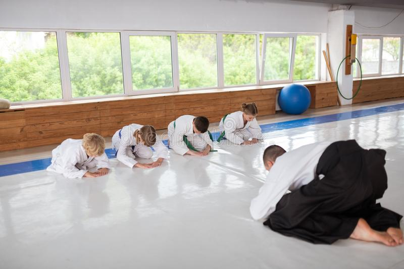 Εκπαιδευτής και παιδιά που χαιρετούν το ένα το άλλο στο μάθημα στοκ εικόνες