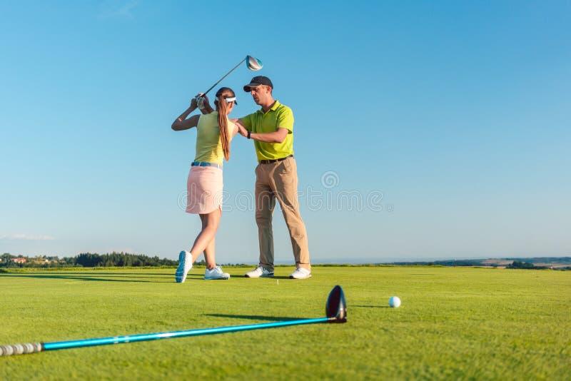 Εκπαιδευτικός γκολφ που διδάσκει μια νέα γυναίκα για να ταλαντευθεί τη λέσχη οδηγών στοκ εικόνες