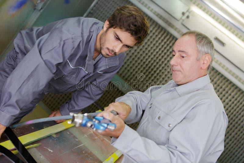 Εκπαιδευόμενος διδασκαλίας εργαζομένων μετάλλων στη χρήση μηχανών στοκ φωτογραφίες με δικαίωμα ελεύθερης χρήσης