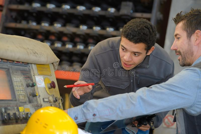 Εκπαιδευόμενος που μαθαίνει πώς να χρησιμοποιήσει τη μηχανή στο εργοστάσιο στοκ φωτογραφία