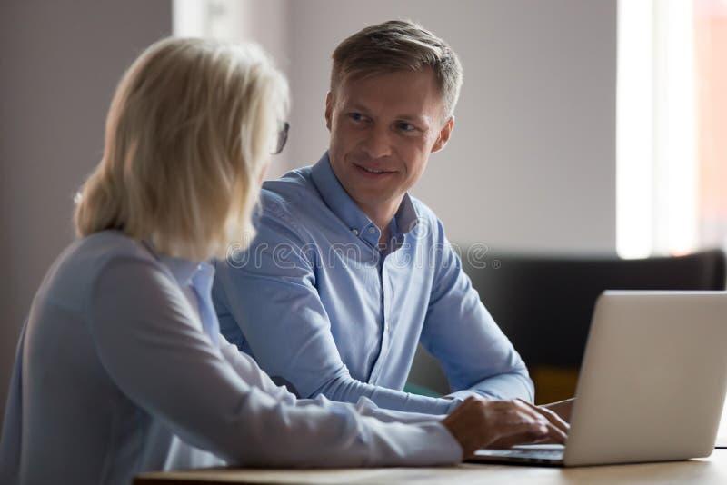 Εκπαιδευόμενος που μιλά με την ώριμη επιχειρηματία, σύμβουλος, που εργάζεται από κοινού στοκ εικόνες