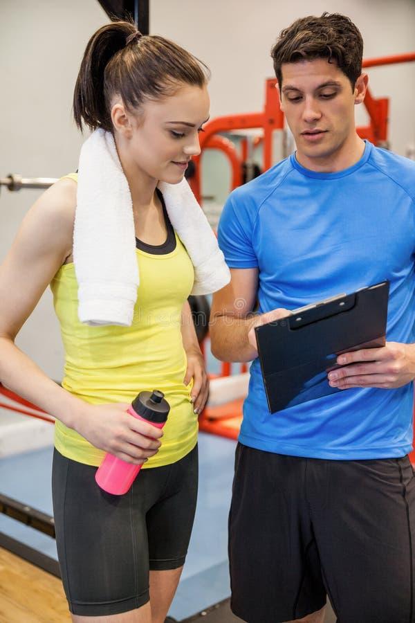 Εκπαιδευτής και γυναίκα που συζητούν workout το σχέδιο στοκ εικόνα