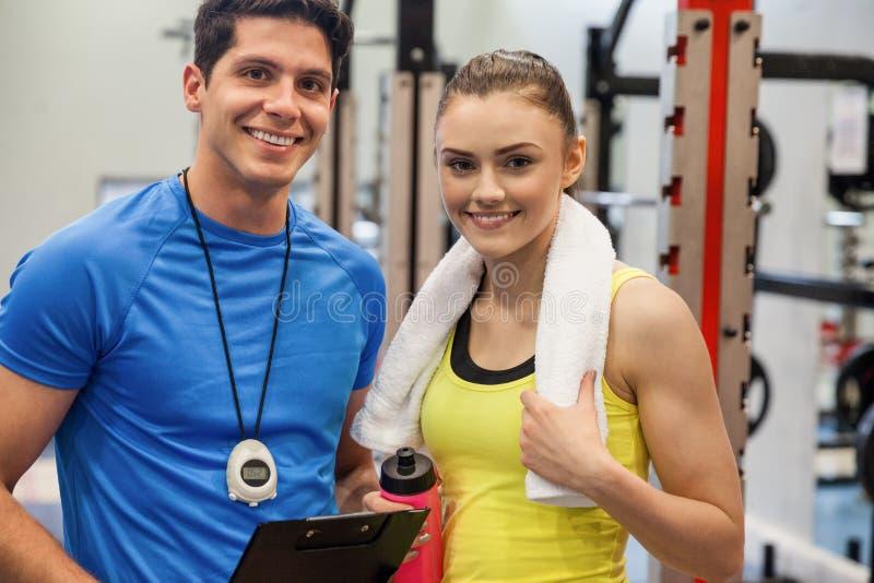 Εκπαιδευτής και γυναίκα που συζητούν workout το σχέδιο στοκ φωτογραφίες με δικαίωμα ελεύθερης χρήσης