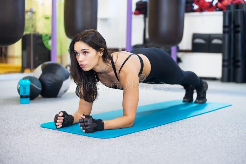 Εκπαιδευτική γυναίκα ικανότητας που κάνει την άσκηση πυρήνων σανίδων στοκ εικόνα