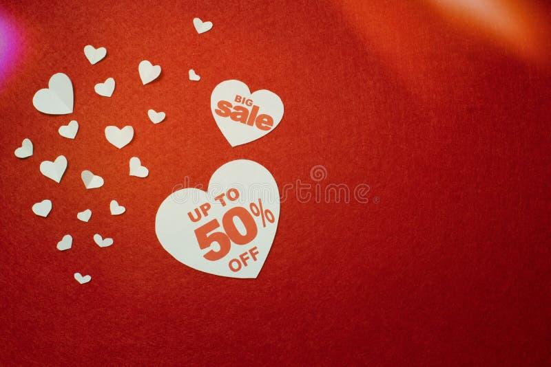 Εκπτώσεις πώλησης στο συμπαθητικού και χαριτωμένου σχέδιο καρδιών, μείον 50, στο κόκκινο υπόβαθρο στοκ εικόνες με δικαίωμα ελεύθερης χρήσης