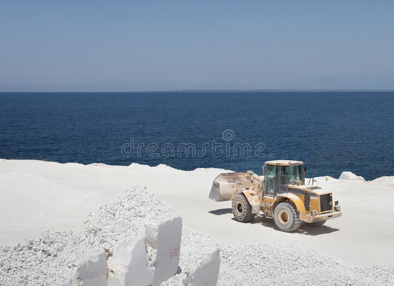 Εκσακαφέας στο μαρμάρινο λατομείο στο νησί στοκ εικόνα