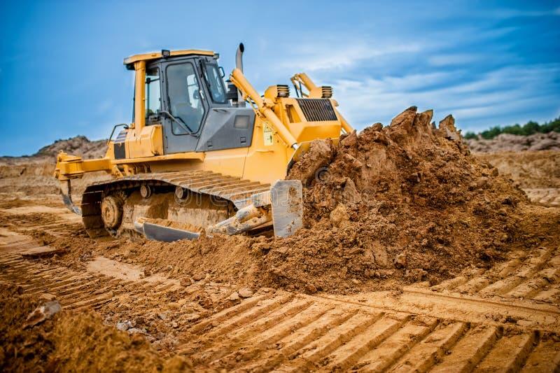 Εκσκαφέας που λειτουργεί με τη γη και την άμμο στο σκάμμα στοκ εικόνες