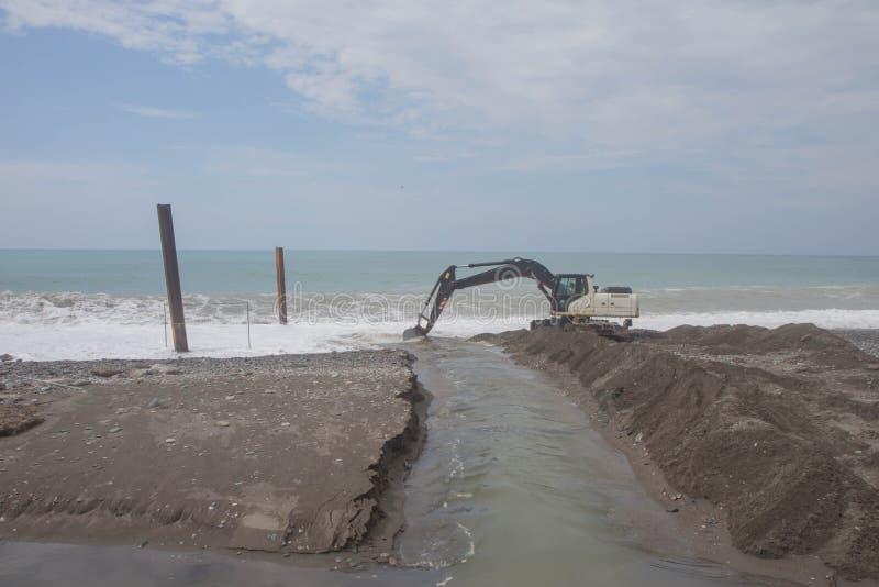 Εκσκαφέας που λειτουργεί στην παραλία για να λειάνει την άμμο πριν από τη θερινή περίοδο αρχή στοκ εικόνα