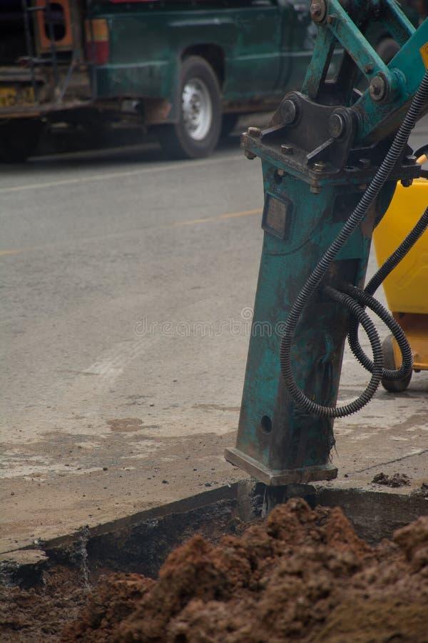 Εκσκαφέας που σπάζει και που τρυπά το συγκεκριμένο δρόμο με τρυπάνι στοκ εικόνα με δικαίωμα ελεύθερης χρήσης