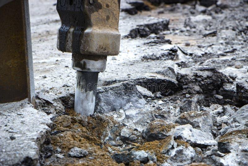 Εκσκαφέας που σπάζει και που τρυπά το συγκεκριμένο δρόμο για την επισκευή με τρυπάνι στοκ εικόνες με δικαίωμα ελεύθερης χρήσης