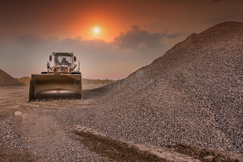 Εκσκαφέας σε ένα λατομείο του μετασχηματισμού πετρών στο αμμοχάλικο για την κατασκευή ενός δρόμου στοκ εικόνα